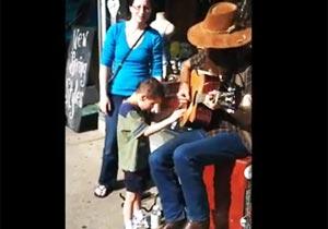 ギターに寄り添う自閉症の少年
