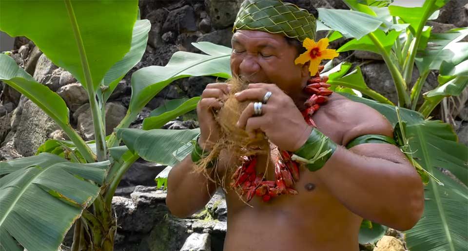 ココナツの殻の剥き方をレクチャーするポリネシアの男