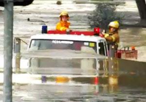 冠水道路を進む消防車