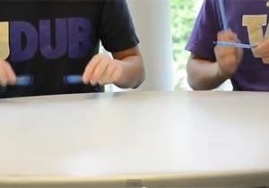 ペンでテーブルを叩く2人の学生