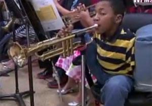 足を使ってトランペットを吹く少年