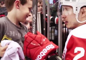 スティックを少年にあげるアイスホッケー選手