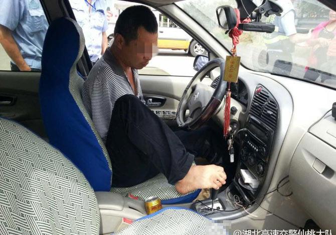 両腕がなく両足で運転する男性